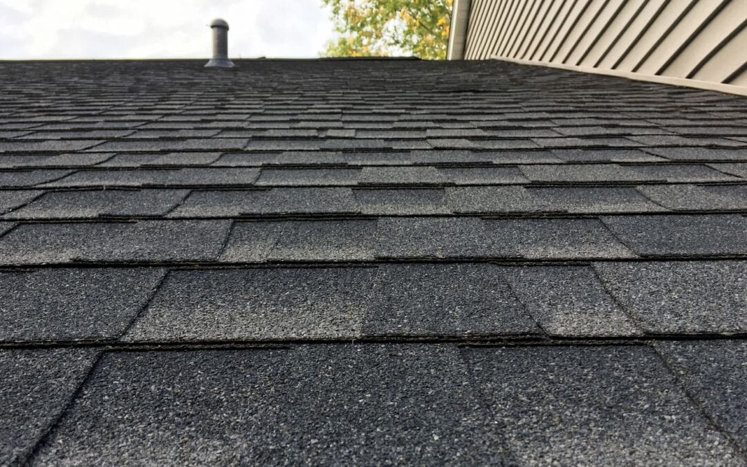 Asphault shingles on a roof up close.